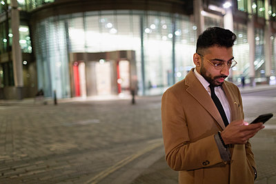 Businessman texting with smart phone on urban street corner at night - p1023m2017152 by Paul Bradbury