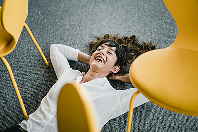 Laughing businesswoman laying in an office on the floor between chairs - p300m2155415 by Kniel Synnatzschke