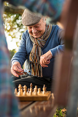 Senior man and grandson playing chess - p300m978212f by Uwe Umstätter