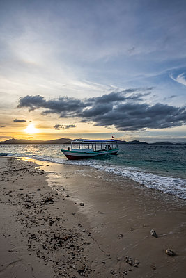 Boat on the beach at sunset, Pulau Kelelawar (Bat Island); West Papua, Indonesia - p442m2154446 by Peter Langer