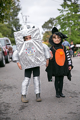 Portrait of boy in robot costume and girl in witch costume on street - p924m1422875 by Sasha Gulish