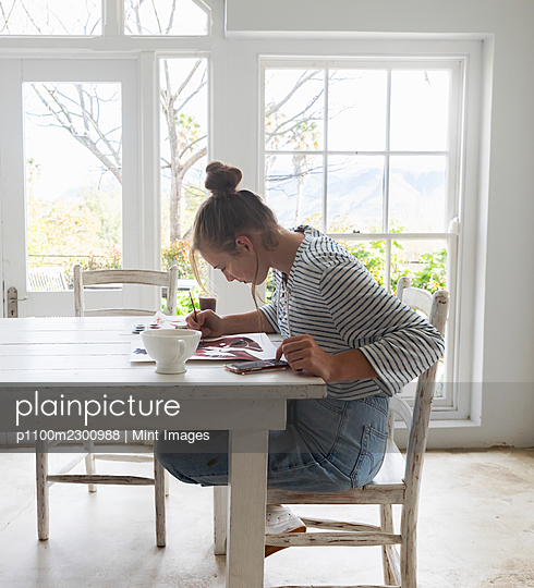 Teenage girl painting with watercolours in a light filled room - p1100m2300988 by Mint Images