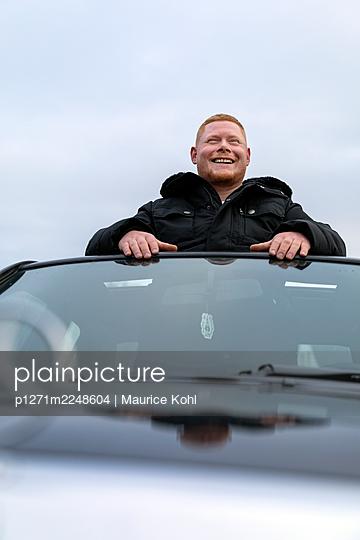 Laughing Mann blickt aus dem Schiebedach eines Autos, Portrait - p1271m2248604 von Maurice Kohl