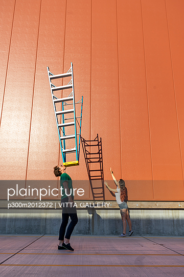 Acrobat balncing ladder on his face while colleague is trying to catch its shadow - p300m2012372 von VITTA GALLERY