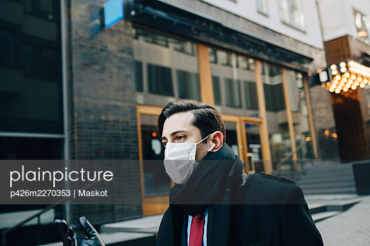 Businessman with scarf standing in city during COVID-19 - p426m2270353 by Maskot