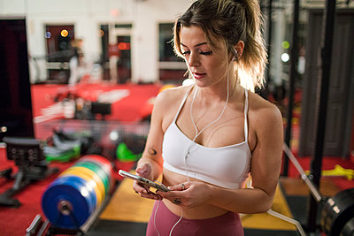 Young woman listening to music with earphones and smartphone at gym - p1166m2084275 by Cavan Images