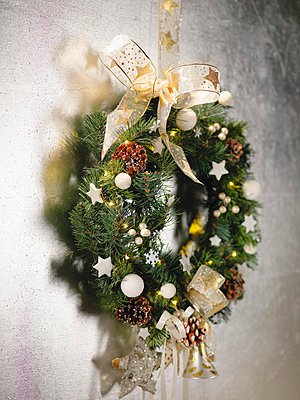 Festively decorated wreath with bow hanging on wall - p1183m997794 by Biglife