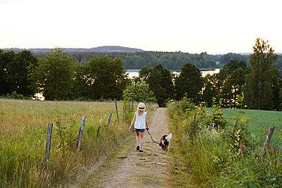 Girl walking dog - p312m2091789 by Anna Kern