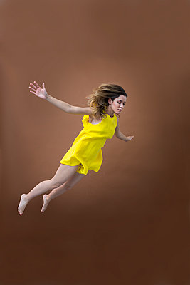 Hovering young woman in yellow dress - p427m2063091 by Ralf Mohr