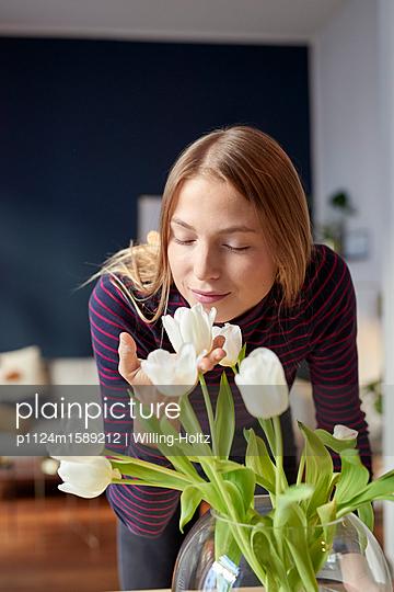 Junge Frau riecht an Tulpen zuhause - p1124m1589212 von Willing-Holtz