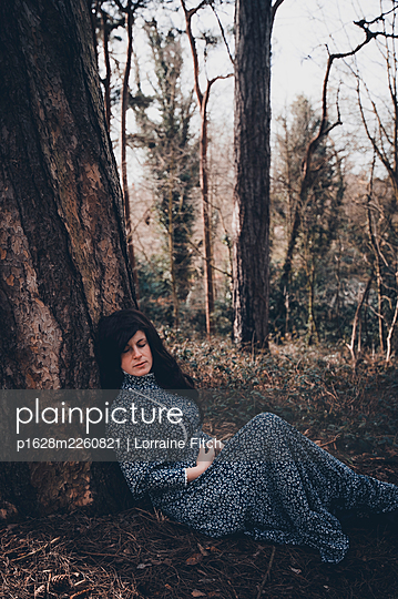 Dark haired woman in green dress leaning against a tree - p1628m2260821 by Lorraine Fitch