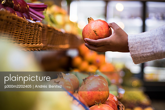 Cropped image of woman buying pomegranate at grocery store - p300m2202405 by Andrés Benitez