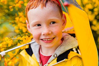 Portrait of redheaded little boy with umbrella - p300m2219449 by Nicole Matthews