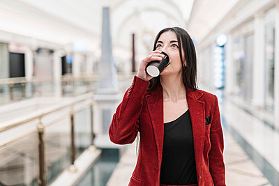 Businesswoman looking up while having coffee at subway station - p300m2266396 by COROIMAGE