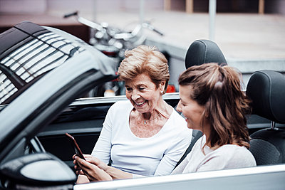 Young woman using mobile phone by grandmother while sitting in car - p300m2274903 by Gustafsson
