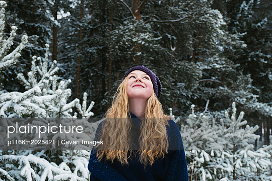 Happy woman with blond hair looking up while standing against trees in forest during winter - p1166m2025421 by Cavan Images