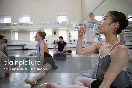 Asian, female ballet dancer drinking water in dance studio