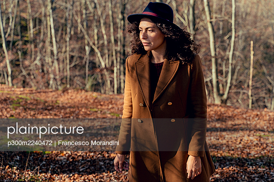 Woman wearing jacket and hat looking away while standing in forest - p300m2240472 by Francesco Morandini