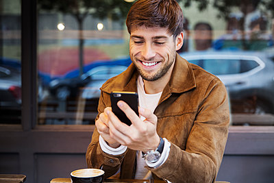 Man with cappuccino using mobile phone while sitting at cafe - p1166m1204402 by Cavan Images