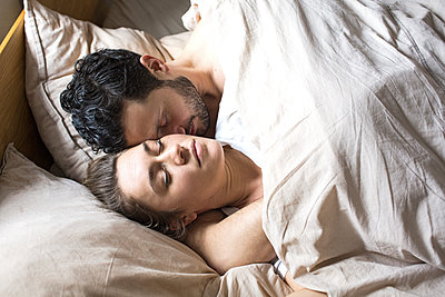 Junges glückliches Paar liegt nebeneinander im Bett  - p1301m1424744 von Delia Baum