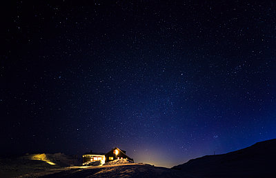 Illuminated house at winter - p312m2092183 by Peter Rutherhagen