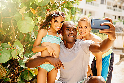 Father and children taking selfie with cell phone outdoors - p555m1408567 by Inti St Clair