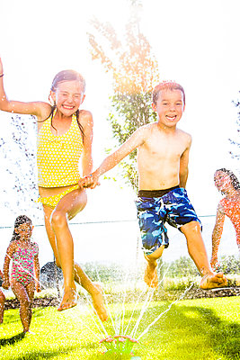 Caucasian children playing in sprinkler in backyard - p555m1415623 by Mike Kemp