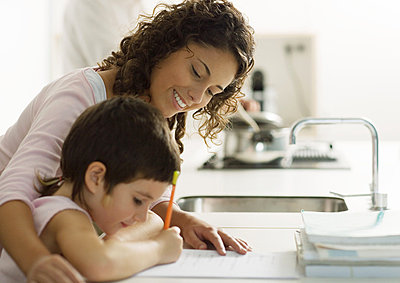 Mother helping child with homework - p6239121f by Laurence Mouton