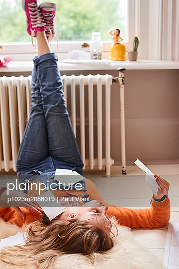 Young female college student studying with flash cards on floor - p1023m2088019 by Paul Viant