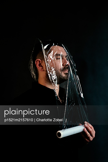 Man with cling film on his face - p1521m2157610 by Charlotte Zobel