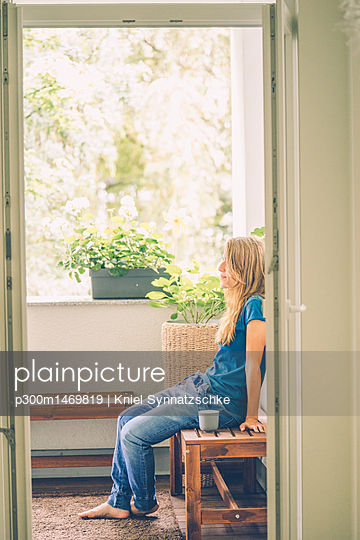 Relaxed young woman sitting on balcony with cup