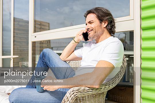 Man holding mug talking on smart phone while sitting on sofa in balcony - p300m2275011 by Jose Carlos Ichiro