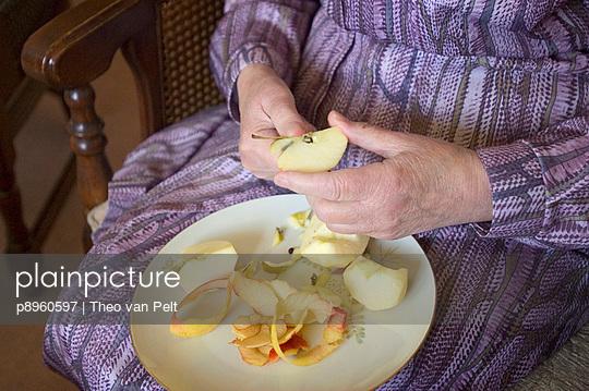 Senior woman cutting an apple - p8960597 by Theo van Pelt