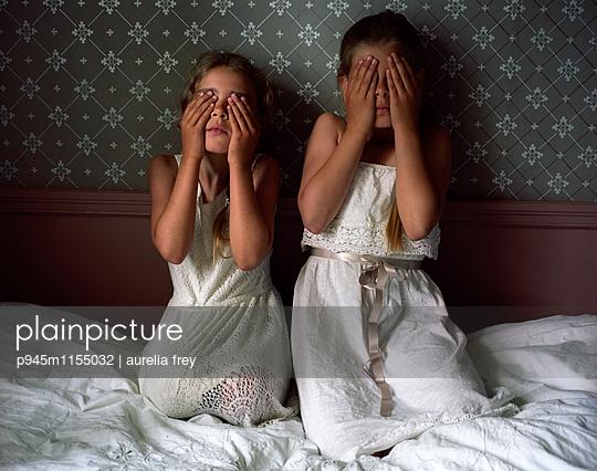 Zwei Mädchen verdecken ihre Augen mit den Händen - p945m1155032 von aurelia frey