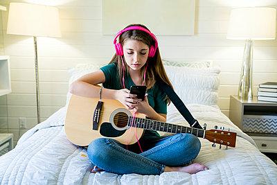 Teenage girl using smart phone while sitting with guitar in bedroom - p1166m1489038 by Cavan Images