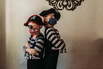 School age brothers dressed as pirates with face masks on at home - p1166m2207771 by Cavan Images