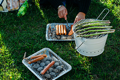 Man's hands preparing barbecue on bucket - p1264m1448528 by Jeanette Seflin