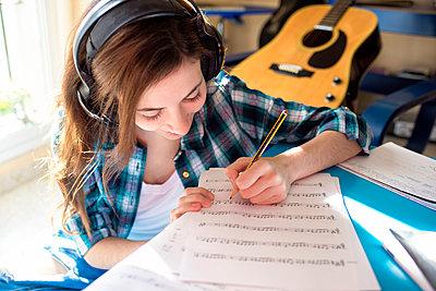 Young woman wearing headphones writing on music sheet - p300m1113576f by Kiko Jimenez