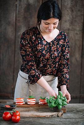 Woman preparing Caprese Salad - p300m2012401 von Alberto Bogo