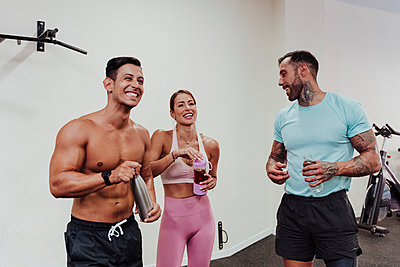 Cheerful sports people drinking water while standing at gym - p300m2273991 by Eva Blanco