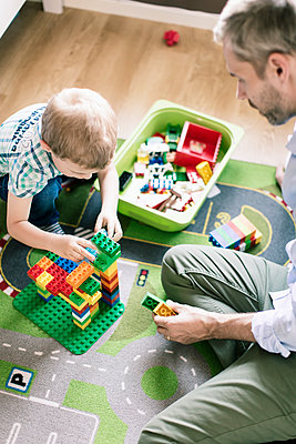 High angle view of father assisting son while playing toy blocks at home - p426m1179357 by Kentaroo Tryman
