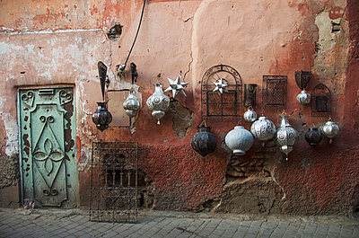 Decorative baubles and metal wall art on display on old wall, Medina, Marrakech, Morocco - p442m784441 by Diane Levit