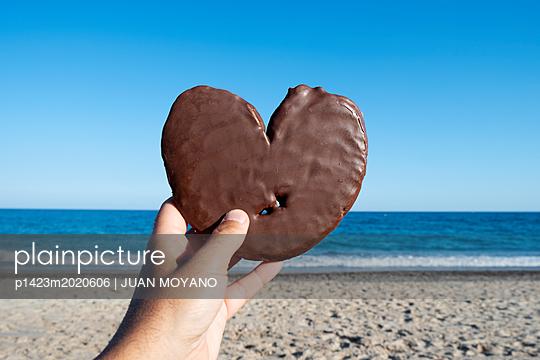 Hand hält Schokoladenherz am Strand - p1423m2020606 von JUAN MOYANO