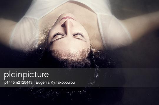 Junge Frau treibt im Wasser - p1445m2128449 von Eugenia Kyriakopoulou