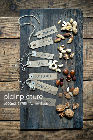 Assorted nuts with labels on wooden table - p300m2131755 by Achim Sass