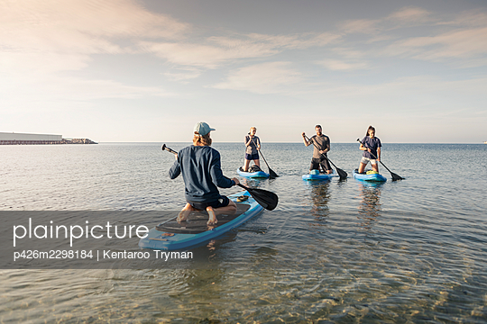 Male instructor teaching paddleboarding to man and women in sea during vacation - p426m2298184 by Kentaroo Tryman