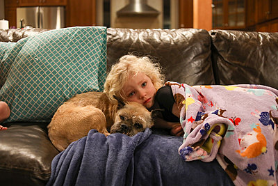 Portrait of girl with dog lying on sofa at home - p1166m1543931 by Cavan Images