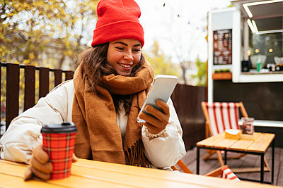 Smiling young woman using mobile phone while sitting at sidewalk cafe - p300m2267179 by alev