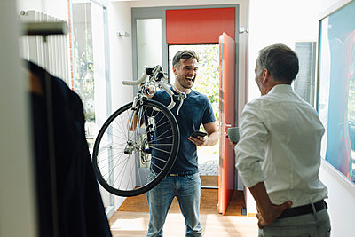 Cheerful son carrying bicycle looking at father while standing at home - p300m2275087 by Gustafsson