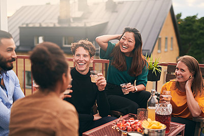 Cheerful friends talking while enjoying social gathering on terrace - p426m2074558 by Maskot